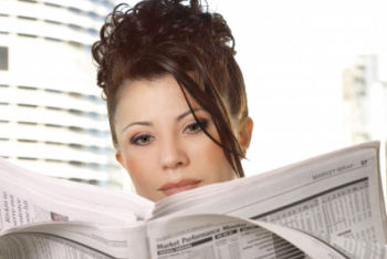 woman reading financial section of newspaper